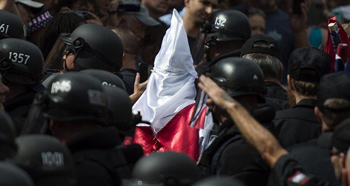 Polícia escolta membro do grupo supremacista branco Ku Klux Klan (KKK)