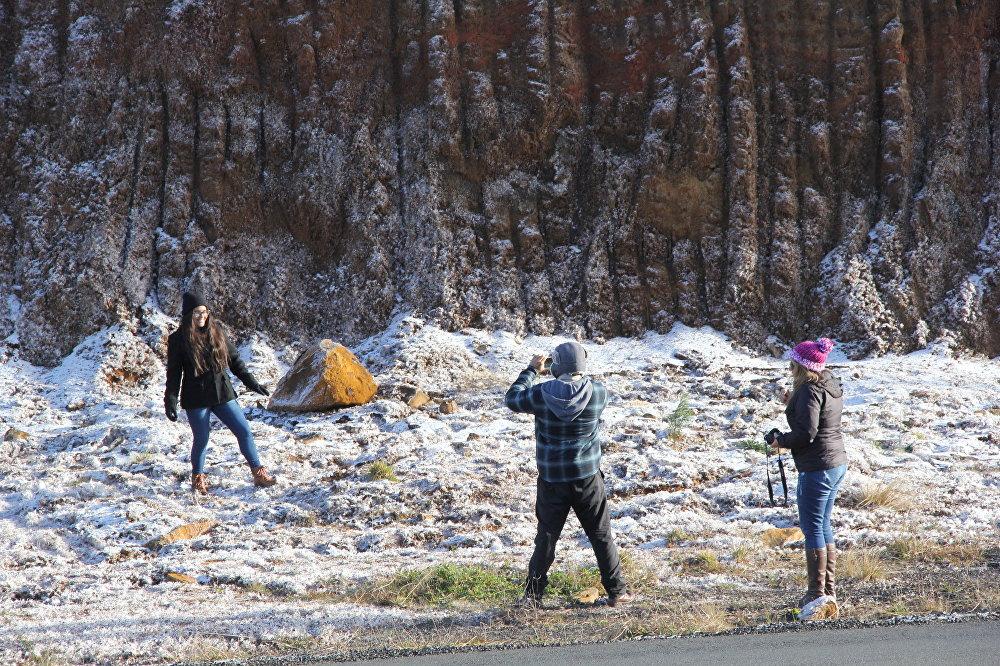 Turistas aproveitam para tirar fotos nas paisagens brancas e congeladas de Santa Catarina