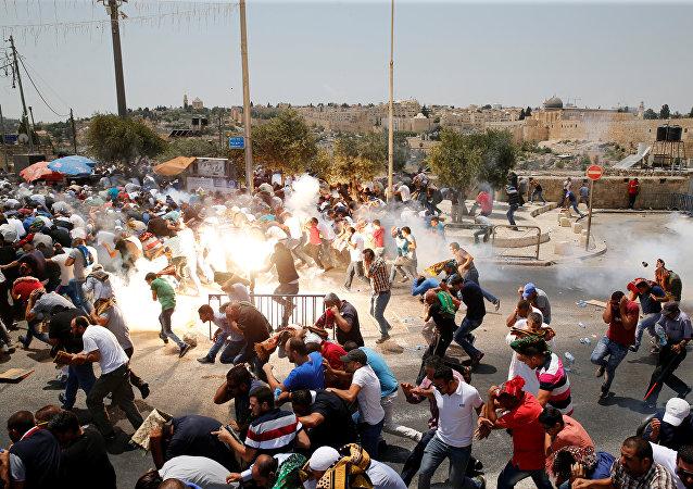 Palestinos fogem após polícia de Israel ter usado gás lacrimogêneo para dispersar multidão de fiéis durante manifestação de 21 de juhlo de 2017