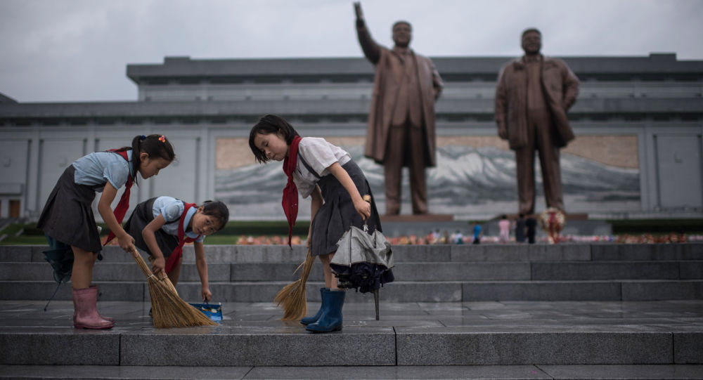 Crianças limpam os degraus perto dos monumentos de Kim Jong-il e Kim Il-sung na Coreia do Norte, no âmbito dos festejos do Dia da Vitória