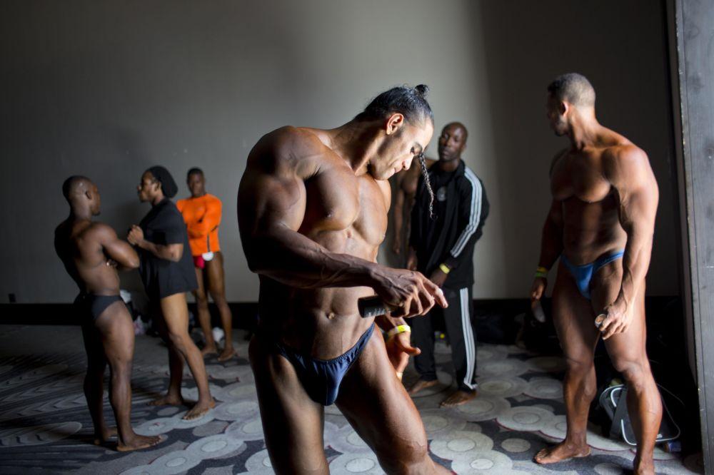 O atleta dominicano Jose Solano atrás dos bastidores antes do começo de um concurso entre culturistas haitianos e dominicanos