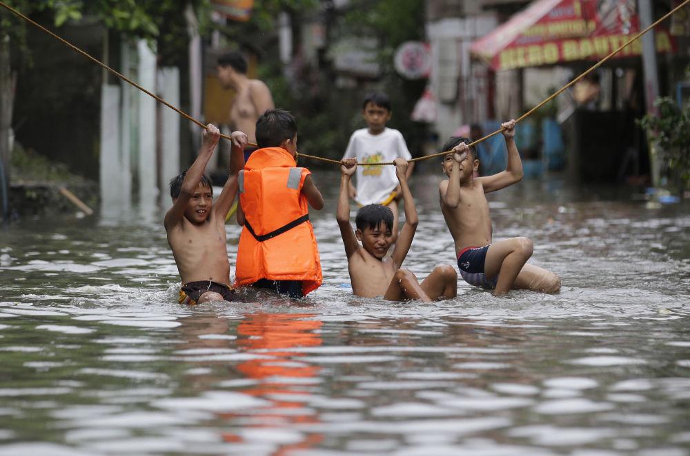 Meninos brincam na rua após a tempestade Nesar em Manila, capital filipina