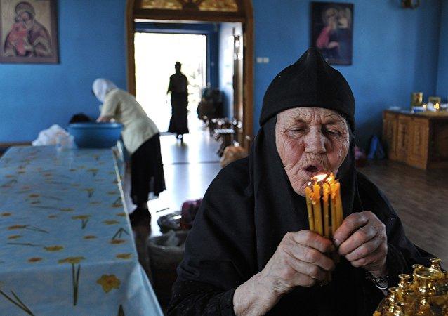 Uma noviça com velas em uma igreja na cidade russa de Rostov-no-Don