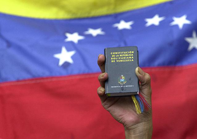 Um manifestante segurauma cópia em miniatura da constituição da Venezuela em frente à bandeira da nação durante uma manifestação do governo em Caracas, Venezuela, terça-feira, 13 de abril de 2004 (foto de arquivo).