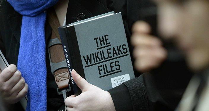 Simpatizante do fundador do WikiLeaks Julian Assange segurando uma cópia do The WikiLeaks Files