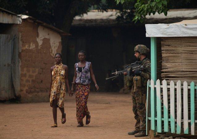 Mulheres andam de mãos dadas perto de soldado francês na República Central-Africana