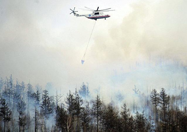 Helicóptero do Ministério para Situações de Emergência russo extinguindo incêndios florestais na Sibéria