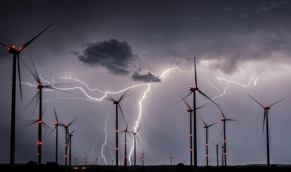 Relâmpagos cruzam o céu por cima dos moinhos de vento de um parque eólico no leste da Alemanha