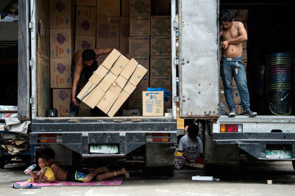Crianças descansam debaixo de um caminhão que está sendo descarregado na cidade filipina de Manila