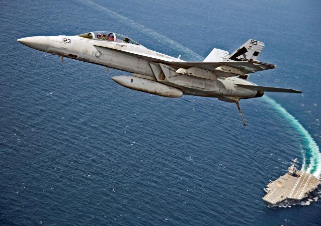 Um caça-bombardeiro americano F/A-18F Super Hornet sobrevoa o porta-aviões da Marinha dos EUA USS Gerald R. Ford, enquanto este testa seus novos sistemas EMALS e AAG no Atlântico