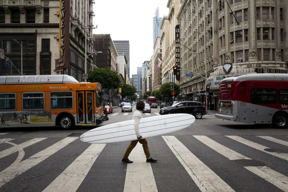 Homem atravessa uma rua no centro da cidade americana de Los Angeles segurando prancha de surfe