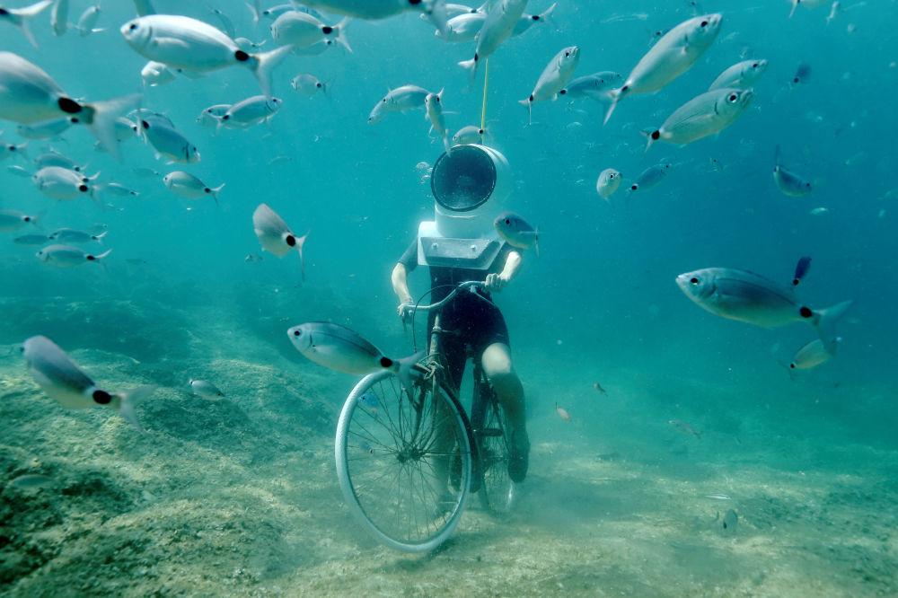 Uma mulher mergulha e finge estar dirigindo uma bicicleta no parque subaquático em Pula, na Croácia
