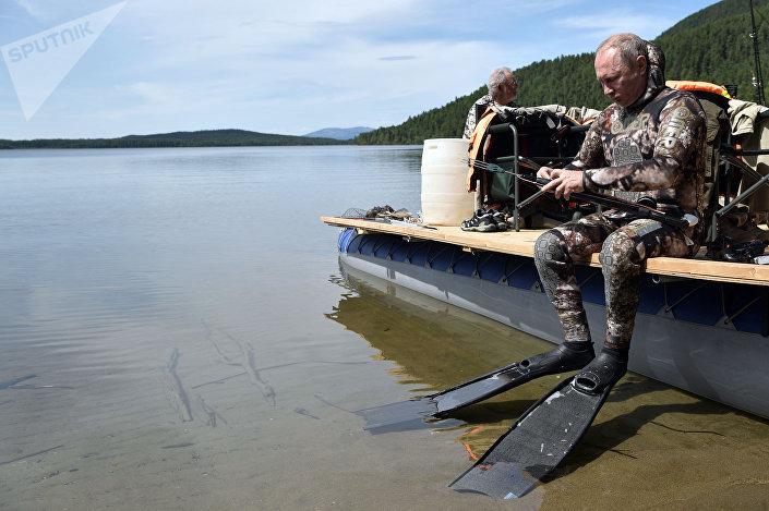 O presidente russo se prepara para o mergulho durante a pesca subaquática em um dos lagos de montanha na república de Tuva