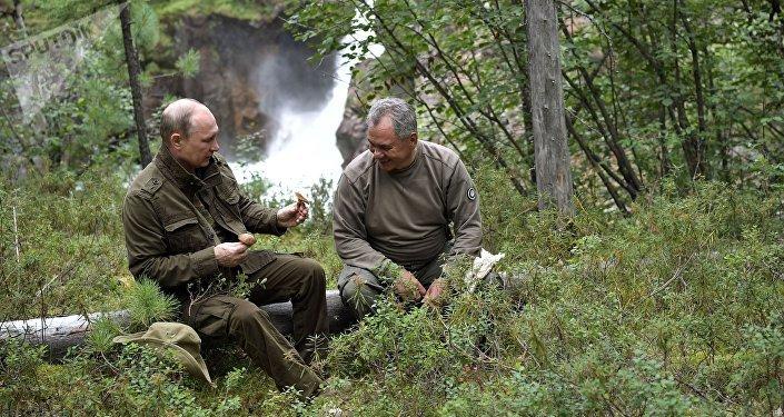 O presidente russo Vladimir Putin e o ministro da Defesa Sergei Shoigu passeiam pelas montanhas na república de Tuva