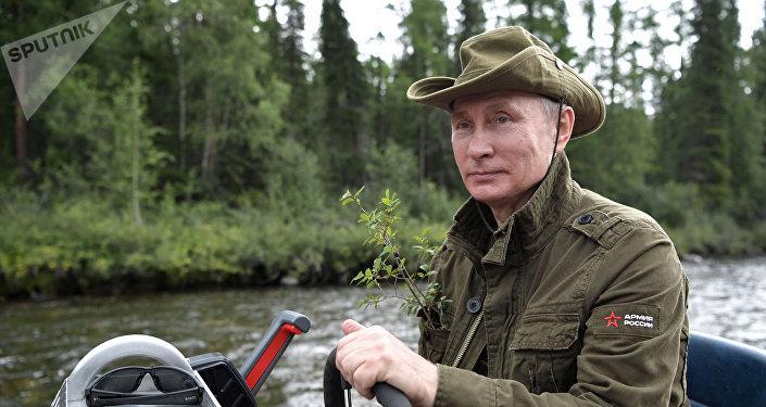 Vladimir Putin dirige um barco a motor russo durante passeio por um dos lagos de montanha, na república de Tuva, durante suas breves férias de verão