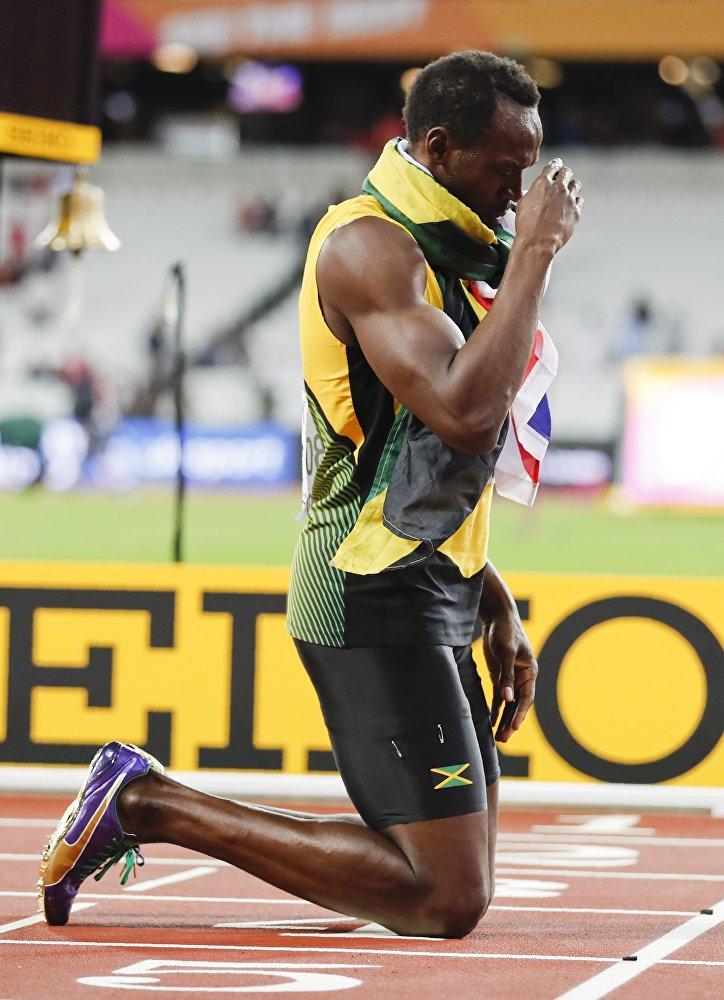 Usain Bolt da Jamaica se ajoelha após a corrida.