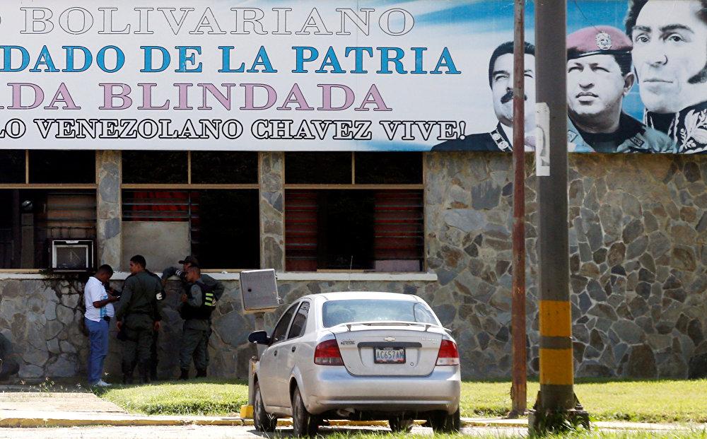 Membros das forças de segurança sob retratos do presidente da Venezuela, Nicolás Maduro, do ex-presidente Hugo Chávez e do herói nacional da Venezuela, Simon Bolivar, fora da base militar da Brigada Blindada Fuerte Paramacay, em Valência, Venezuela, em 6 de agosto de 2017.