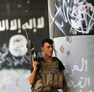 Soldado iraquiano em frente à pichação do Daesh
