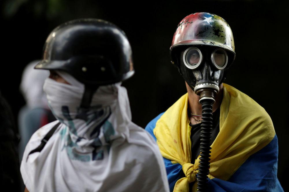 Manifestantes com máscaras de gás durante um protesto contra o presidente venezuelano Nicolás Maduro em Caracas