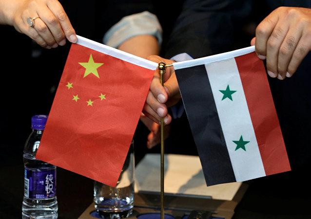 Empresários sírios e chineses exibem bandeiras dos dois países durante encontro em Pequim para discutir projetos de reconstrução da Síria