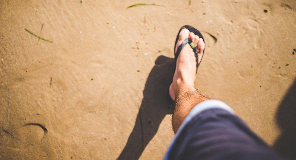 Homem caminhando pela praia (foto de arquivo)