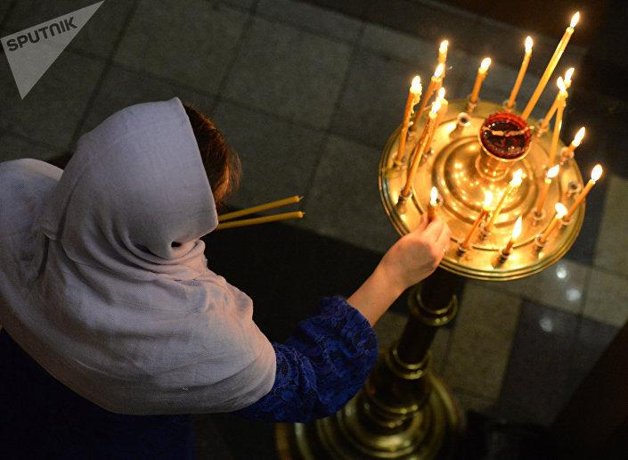 Uma cristã ortodoxa russa colocando velas