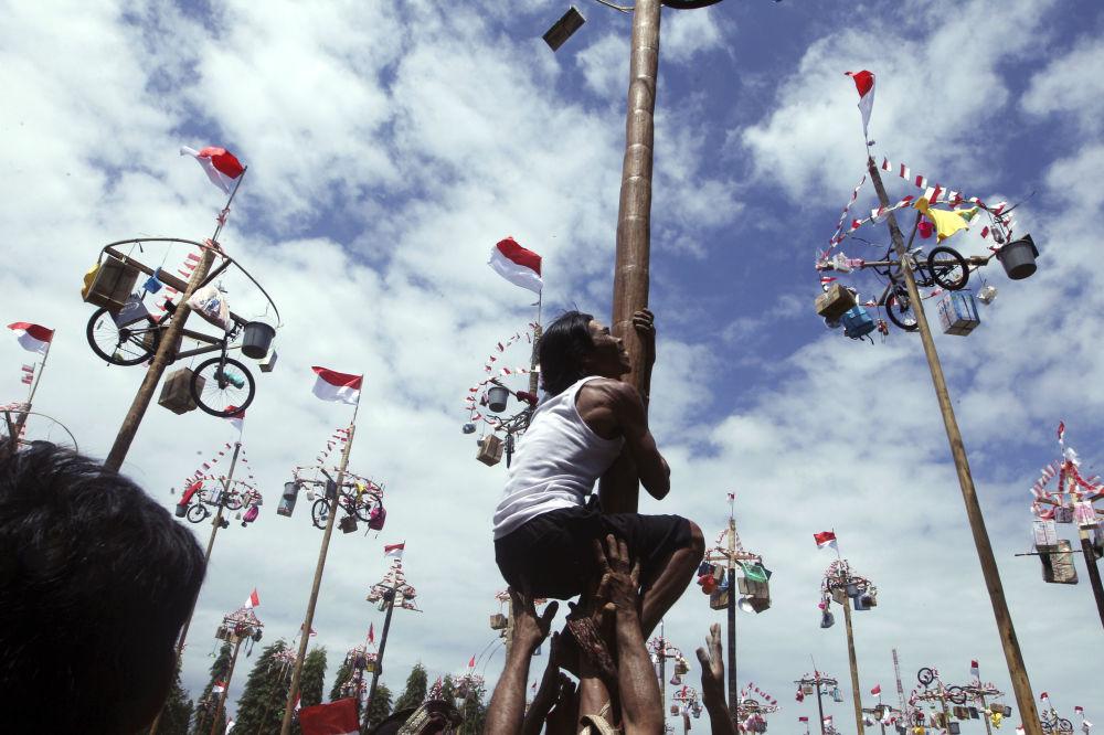 Homem tenta subir ao topo do poste para ganhar bicicleta. A competição é realizada por ocasião do Dia da Independência, Bali, Indonésia