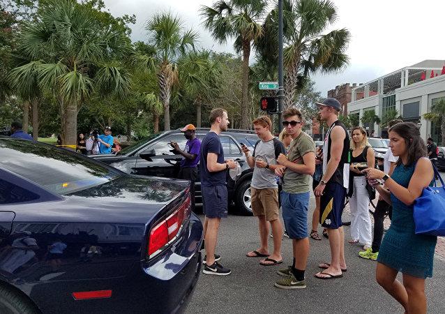 Curiosos aguardam liberação de perímetro estabelecido pela polícia de Charleston após tiroteio em restaurante