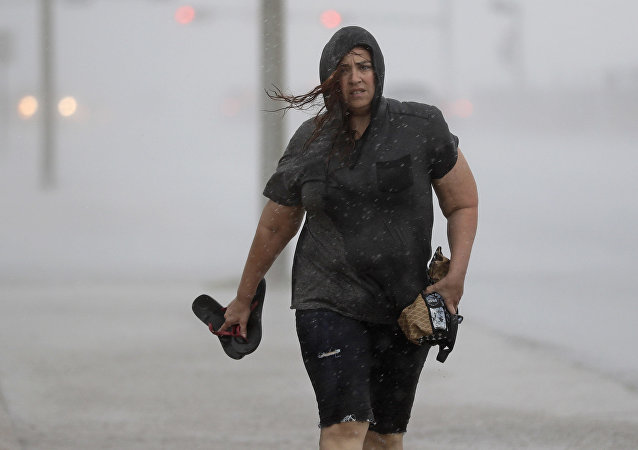 Hillary Lebeb walks along the seawall in Galveston, Texas as Hurricane Harvey intensifies in the Gulf of Mexico Friday, Aug. 25, 2017.