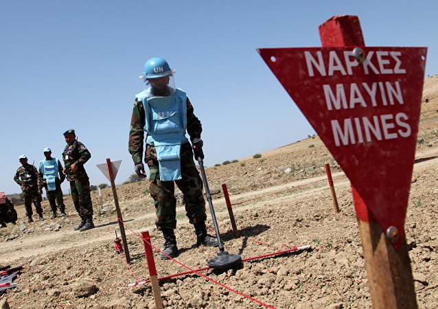An UNIFIL's Cambodian mine expert demonstrates his work on April 23, 2014 in the UN-controlled buffer zone, where demining operations are being conducted under the auspices of the United Nations Peacekeeping Force in Cyprus (UNFICYP), near the village of Mammari