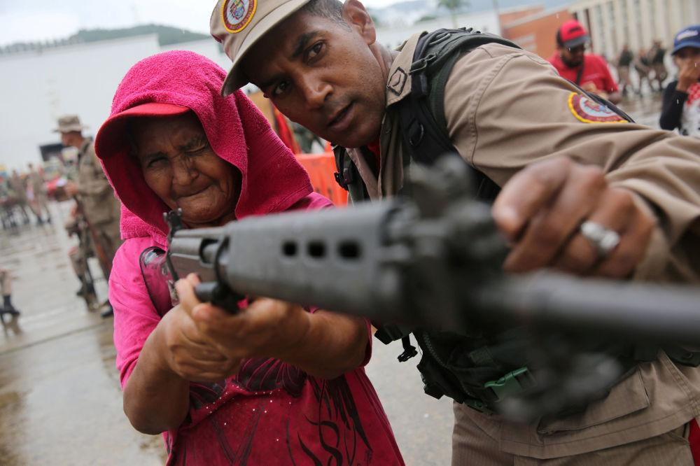 Policial das Forças Armadas venezuelanas ensina mulher como usar fuzil durante exercícios militares em Caracas