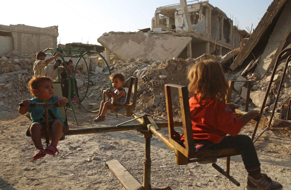Crianças brincam no bairro destruído da cidade síria de Douma