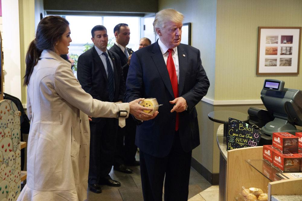 Hope Hicks entregando uma caixa de biscoitos para Donald trump durante um evento no âmbito da campanha eleitoral de Trump, em 10 de outubro de 2016