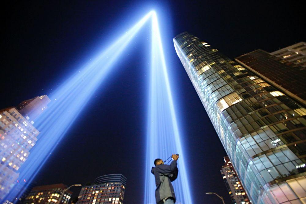 """Homem tira fotos da iluminação Tributo em Luz (""""Tribute in Light"""") em memória dos atentados de 9/11, em Nova York"""