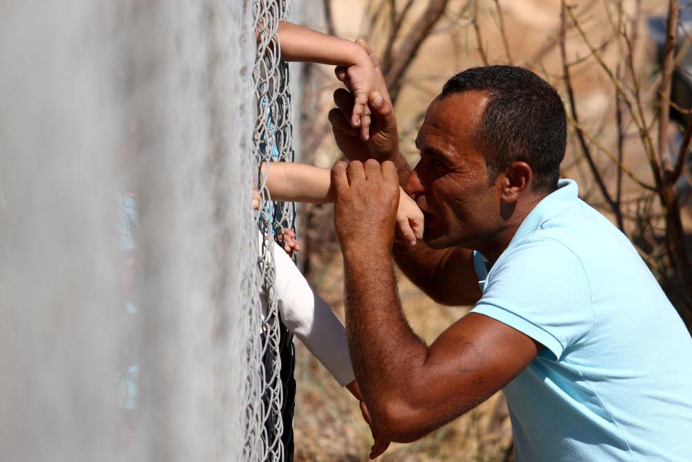 Ammar Hammasho, um sírio que reside no Chipre, beija seus filhos que vieram ao campo de refugiados em Kokkinotrimithia