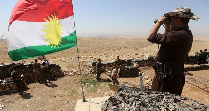 Bandeira do Curdistão e combatente curdo Peshmerga monitorando a área a partir do seu posto na linha de frente em Bashiqa