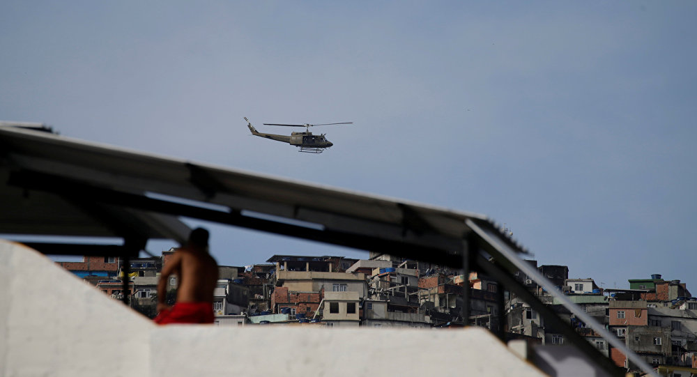 A military helicopter flies overhead during an operation after violent clashes between drug gangs in Rocinha slum in Rio de Janeiro, Brazil