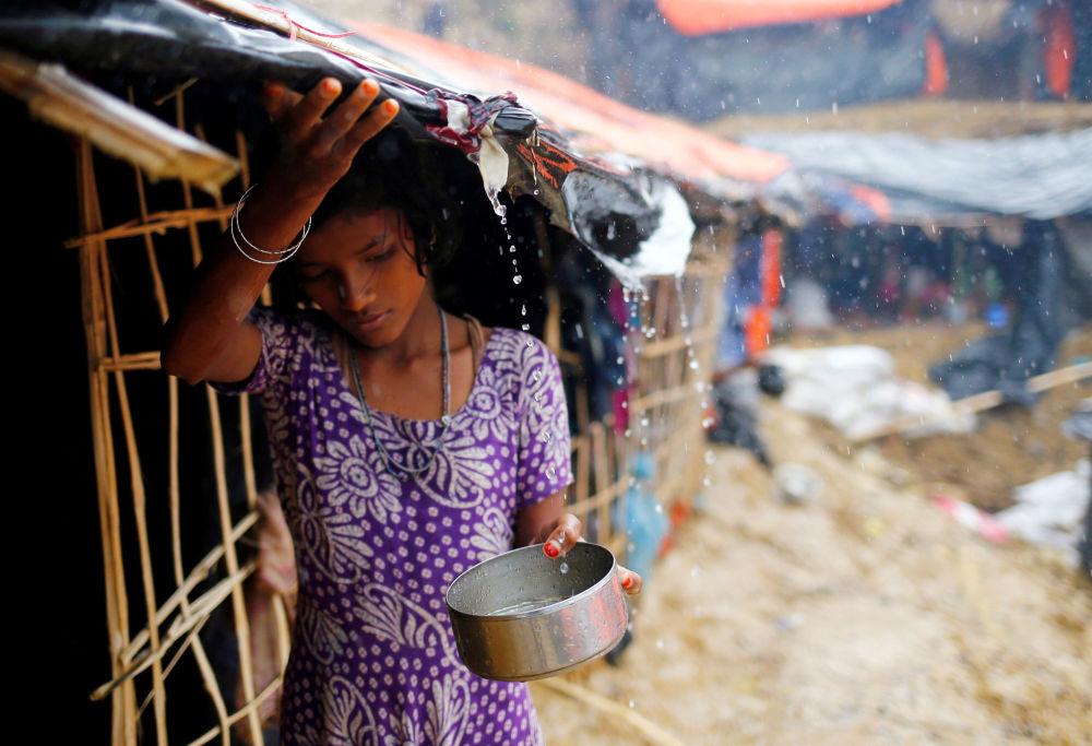 Menina rohingya recolhe água da chuva no campo de refugiados em Cox's Bazar, Bangladesh