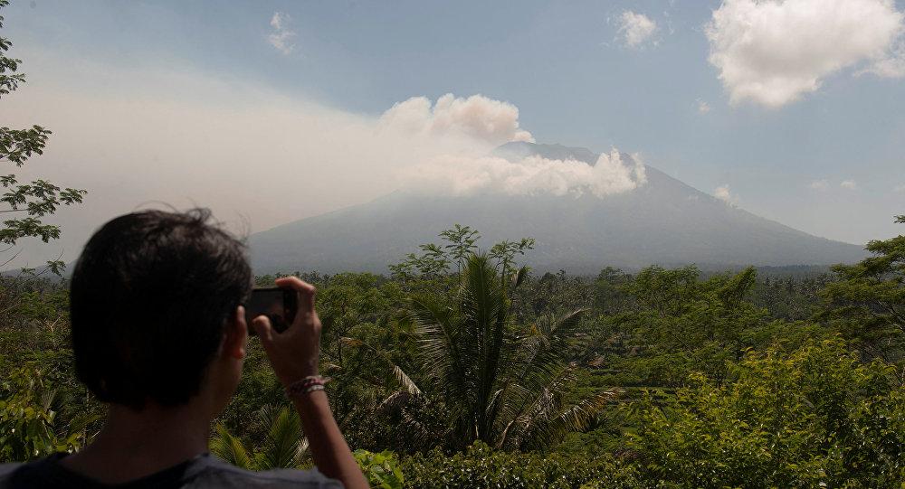 Homem tira foto do monte Agung, um importante vulcão localizado na ilha de Bali, na Indonésia