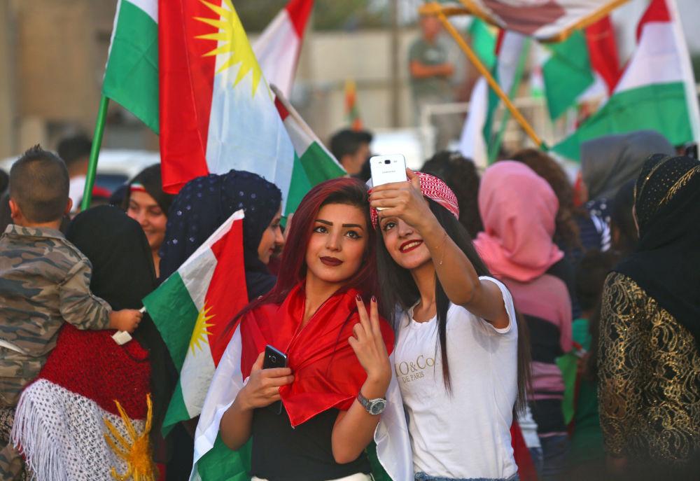 Curdas sírias tirando selfie durante as celebrações a favor do referendo curdo