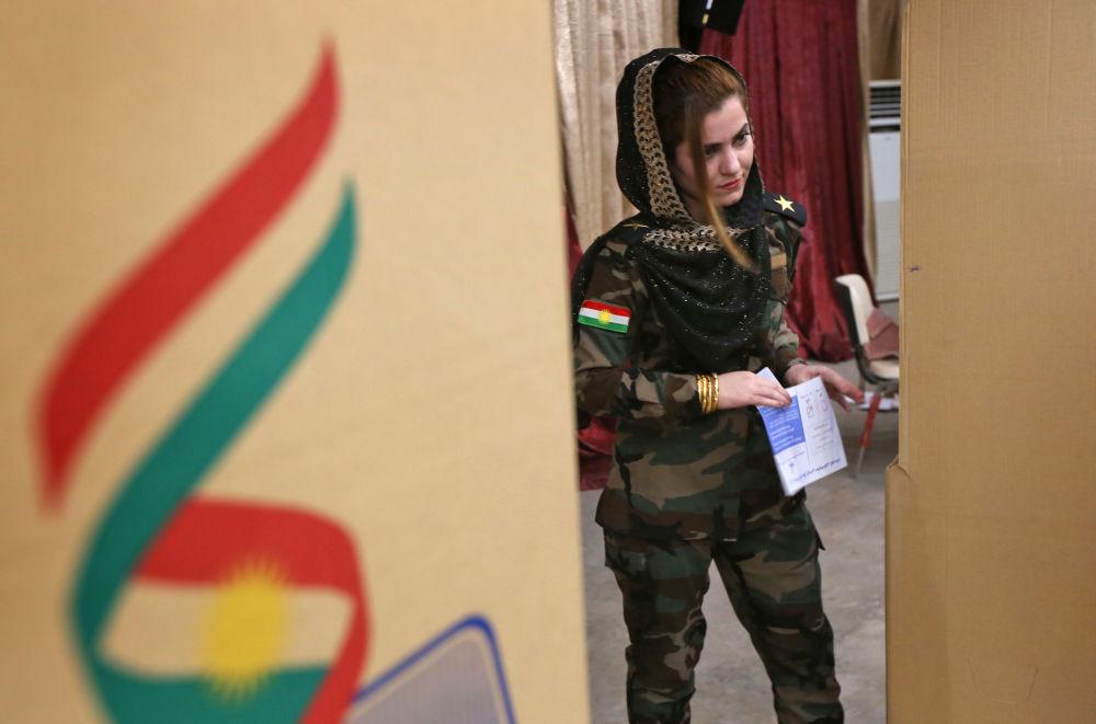 Uma mulher das forças peshmerga votando durante o referendo numa mesa de voto em Erbil