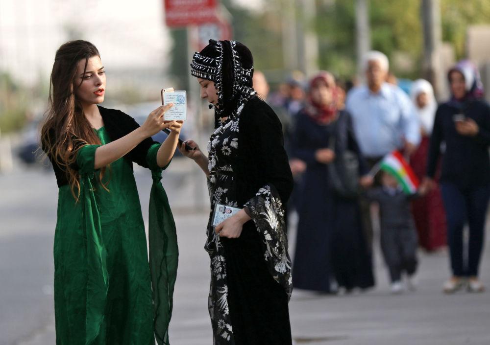 Curdas com suas cédulas de identidade enquanto se dirigem à mesa de voto, em Erbil