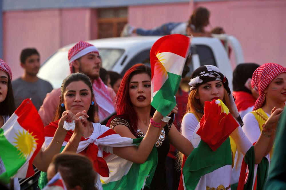 Curdas sírias dançando com a bandeira curda durante celebrações a favor do referendo no Curdistão iraquiano