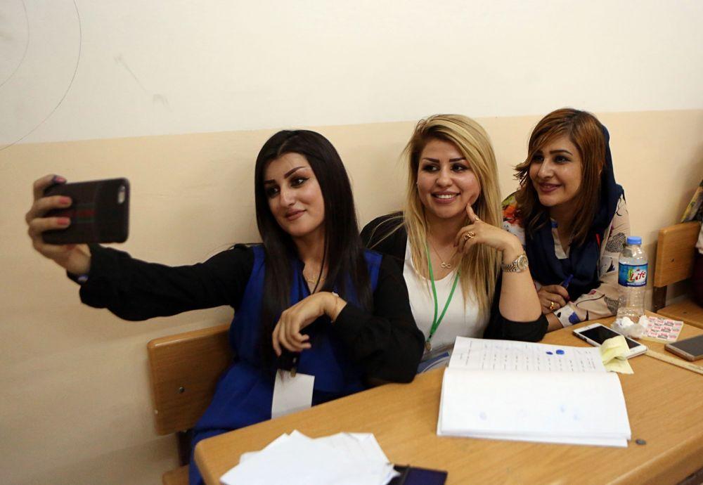 Membros da mesa de voto tirando uma foto em um local de votação no Iraque durante o referendo curdo