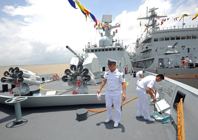 Crew members work on the Chinese Navy ship Wei Fang as it docks at the Myanmar International Terminal Thilawa (MITT) port on the outskirts of Yangon on May 23, 2014