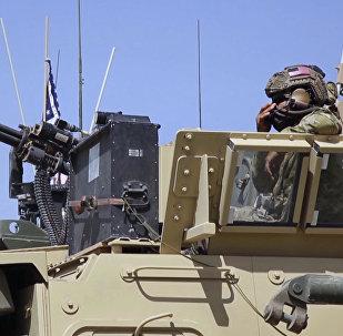 Militar estadunidense vigia área em veículo blindado na Síria