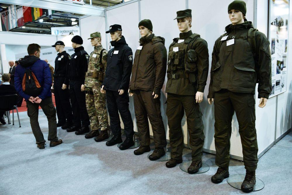 Homem examina diferentes versões de uniformes militares expostas na mostra Armas e Segurança 2017 em Kiev