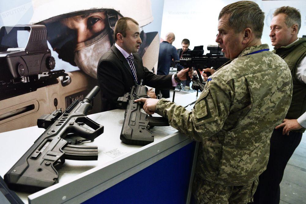 Homem examina armas de fogo na exposição Armas e Segurança 2017 em Kiev