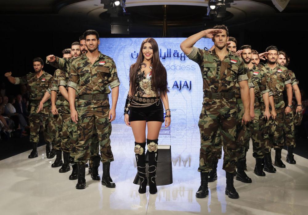 A designer síria Manal Ajaj posa na passarela com homens modelos vestidos com uniformes do exército sírio durante seu show de moda