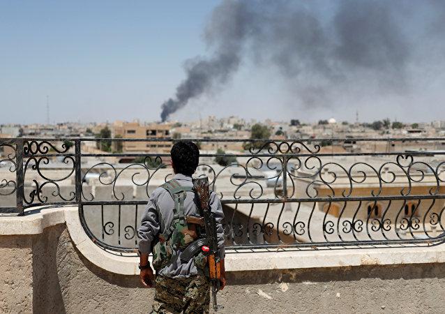 Soldado curdo olhando para fumaça depois de ataques aéreos da coalizão em Raqqa (foto de arquivo)